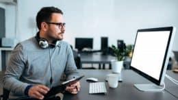 Homme devant un ordinateur et casque